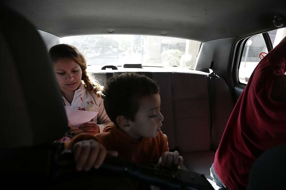 Ines Valencia rides a taxi with her sons, after they were released in San Diego while seeking asylum. Photo: Gregory Bull, Associated Press