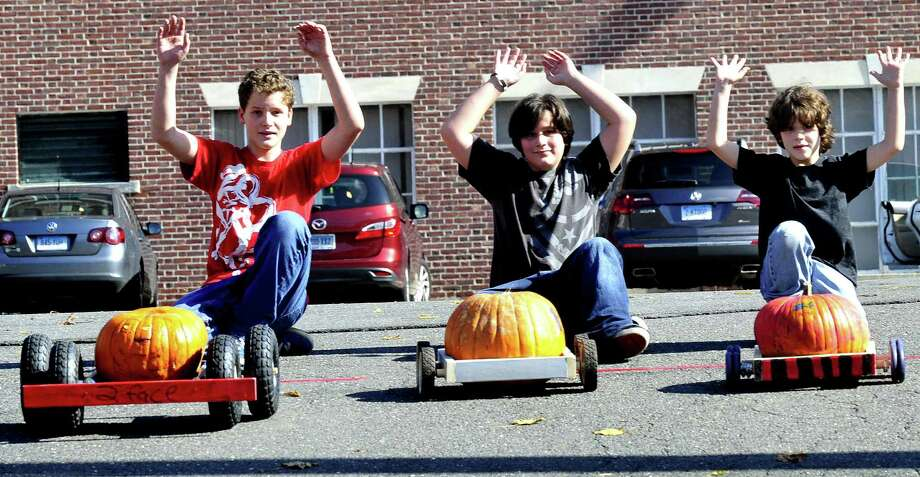 Brothers, Jason Kuzara, 14, left, Drew, 12, and Jason, 9, let their racers roll during Newtown's Great Pumpkin Race Saturday, Oct. 20, 2012. This year's event will be Saturday, Oct. 19, behind Edmond Town Hall in Newtown. Photo: Michael Duffy / The News-Times