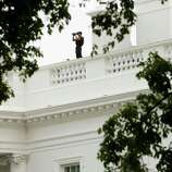 A member of the Secret Service Counter Assault team watches from the roof of the White House in Washington to survey the area, Thursday, Oct. 3, 2013, after reports of shot being fired on Capitol Hill. A police officer was reported injured after gunshots at the U.S. Capitol, police said Thursday. They locked down the entire complex, at least temporarily derailing debate over how to end a government shutdown.