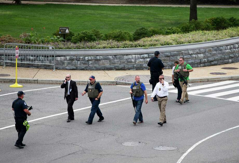 Police and federal agents converge on the scene of a shooting on Constitution Avenue on Capitol Hill near the Supreme Court in Washington, Thursday, Oct. 3, 2013. A police officer was reported injured after gunshots at the U.S. Capitol, police said Thursday. They locked down the entire complex, at least temporarily derailing debate over how to end a government shutdown. Photo: AP