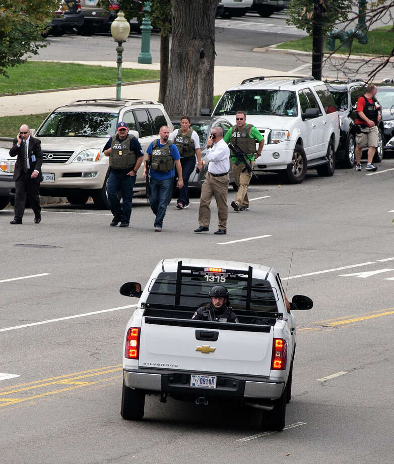 Police and federal agents converge on the scene of a shooting on Constitution Avenue on Capitol Hill and near the Supreme Court in Washington, Thursday, Oct. 3, 2013. A police officer was reported injured after gunshots at the U.S. Capitol, police said Thursday. They locked down the entire complex, at least temporarily derailing debate over how to end a government shutdown. Photo: AP