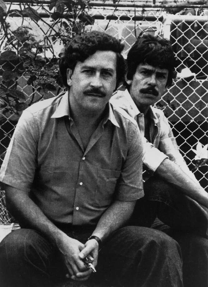 PABLO ESCOBAR, LEFT, THE BILLIONAIRE LEADER OF THE MEDELLIN DRUG CARTEL, POSES AT A SOCCER GAME IN MEDELLIN, COLOMBIA, IN 1983. AT RIGHT IS AN UNIDENTIFIED BODYGUARD. (AP PHOTO). (AP Photo) Photo: AP