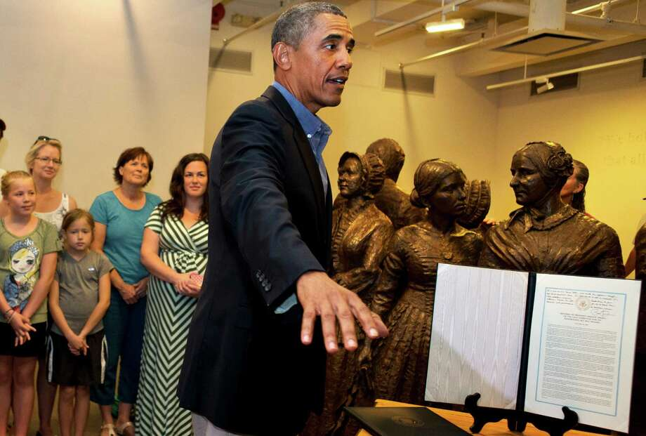 President Barack Obama gestures as he presents a signed copy of the Lilly Ledbetter Fair Pay Act of 2009 and his remarks from the signing center, to the Women's Right National Historic Park, while in their Visitors Center in Seneca Falls on Aug. 22, 2013. (AP Photo) ORG XMIT: MER2013082216254763 Photo: Jacquelyn Martin / AP