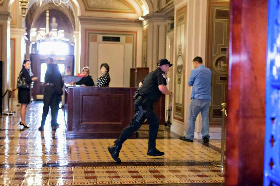 A Capitol Police officer runs through the first floor of the Senate on Capitol Hill in Washington, Thursday, Oct. 3,2013, during the lockdown order following a shooting on Constitution Avenue on Capitol Hll and near the Supreme Court. A police officer was reported injured after gunshots at the U.S. Capitol, police said Thursday. They locked down the entire complex, at least temporarily derailing debate over how to end a government shutdown. Photo: AP