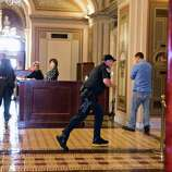 A Capitol Police officer runs through the first floor of the Senate on Capitol Hill in Washington, Thursday, Oct. 3,2013, during the lockdown order following a shooting on Constitution Avenue on Capitol Hll and near the Supreme Court. A police officer was reported injured after gunshots at the U.S. Capitol, police said Thursday. They locked down the entire complex, at least temporarily derailing debate over how to end a government shutdown.