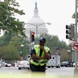 A Washington police officer stands guard on Capitol Hill in Washington, Thursday, Oct. 3, 2013, after a report of a shooting. A police officer was reported injured after gunshots at the U.S. Capitol, police said Thursday. They locked down the entire complex, at least temporarily derailing debate over how to end a government shutdown.
