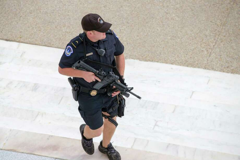 A U.S. Capitol Police officer keeps watch on the steps of the Russell Senate Office Building on Capitol Hill near the Supreme Court in Washington, Thursday, Oct. 3, 2013, after a report of shots fired. A police officer was reported injured after gunshots at the U.S. Capitol, police said Thursday. They locked down the entire complex, at least temporarily derailing debate over how to end a government shutdown. Photo: AP