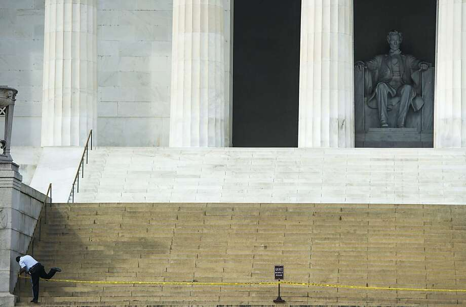 A security guard crosses over police tape at the closed Lincoln Memorial, which was off-limits to visitors during the shutdown. Photo: Jim Watson, AFP/Getty Images