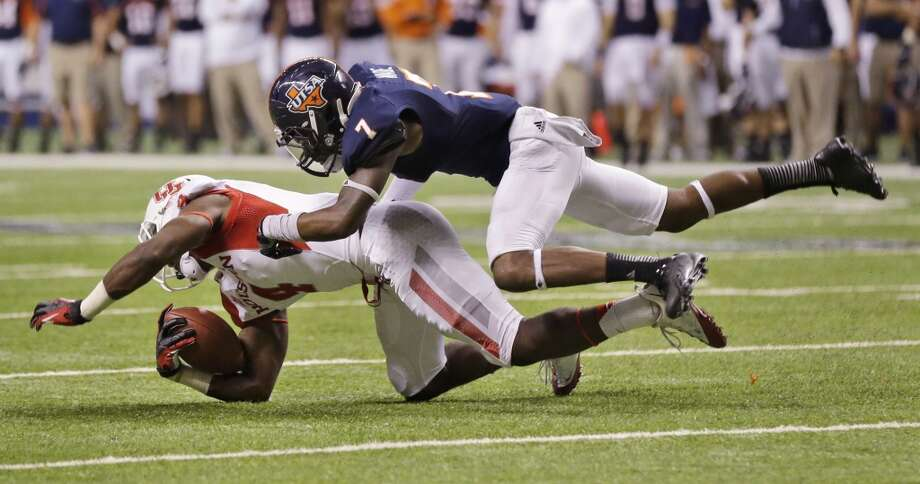 Houston's Daniel Spencer (4) is hit by Texas-San Antonio's Triston Wade after completing the pass during the second half of an NCAA college football game on Saturday, Sept. 28, 2013, in San Antonio. Houston won 59-28. (AP Photo/Eric Gay) Photo: Eric Gay, Associated Press