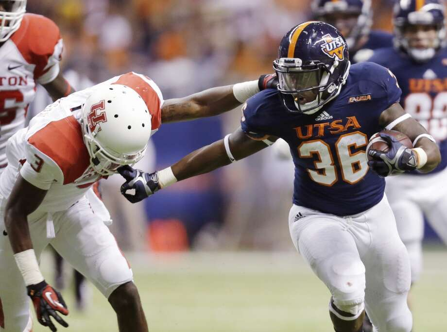 Texas-San Antonio's Evans Okotcha (36) grabs the face mask of Houston defender William Jackson (3) as he runs during the second half of an NCAA college football game, Saturday, Sept. 28, 2013, in San Antonio. (AP Photo/Eric Gay) Photo: Eric Gay, Associated Press