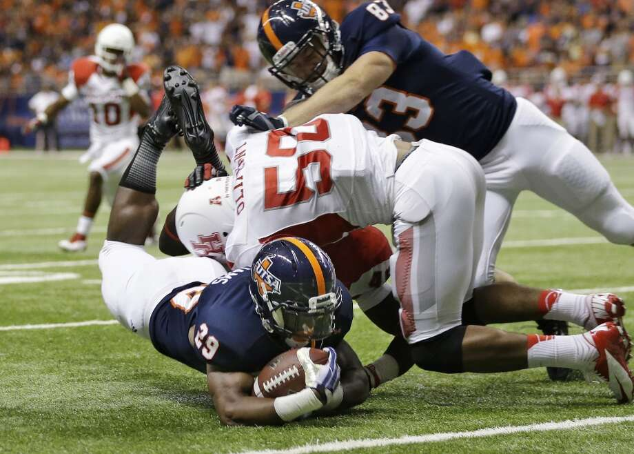 Texas San Antonio's Jarveon Williams (29) is hit by Houston's Efrem Oliphant (50) as he takes the ball to the one yard line to set up a touchdown during the first half of an NCAA college football game, Saturday, Sept. 28, 2013, in San Antonio. (AP Photo/Eric Gay) Photo: Eric Gay, Associated Press