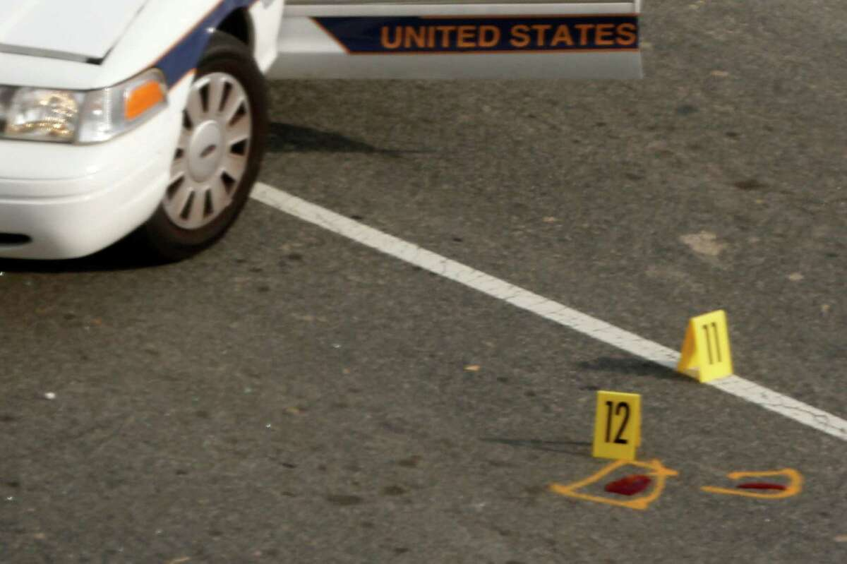 Evidence markers are placed near a Capitol Police vehicle following a shooting on Capitol Hill in Washington, Thursday, Oct. 3, 2013. A police officer was reported injured after gunshots at the U.S. Capitol, police said Thursday. They locked down the entire complex, at least temporarily derailing debate over how to end a government shutdown.