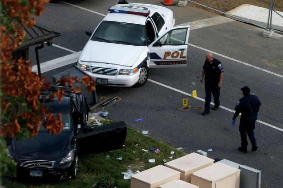 Capitol Hill police officers look at a car following a shooting on Capitol Hill in Washington, Thursday, Oct. 3, 2013. A police officer was reported injured after gunshots at the U.S. Capitol, police said Thursday. They locked down the entire complex, at least temporarily derailing debate over how to end a government shutdown. Photo: AP