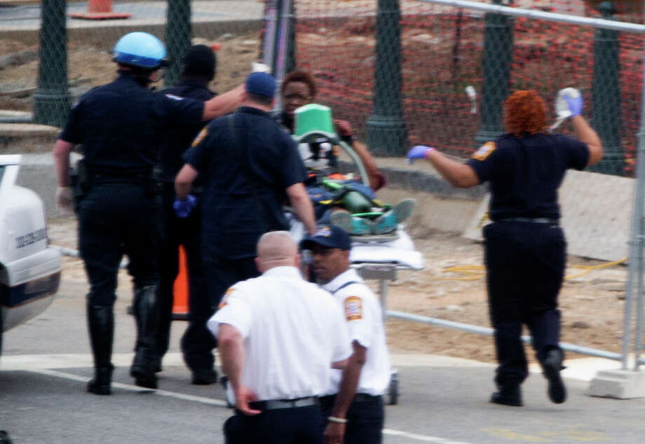 Emergency personal wheel off an injured person after a shooting on Capitol Hill in Washington, Thursday, Oct. 3, 2013. A police officer was reported injured after gunshots at the U.S. Capitol, police said Thursday. They locked down the entire complex, at least temporarily derailing debate over how to end a government shutdown. Photo: AP