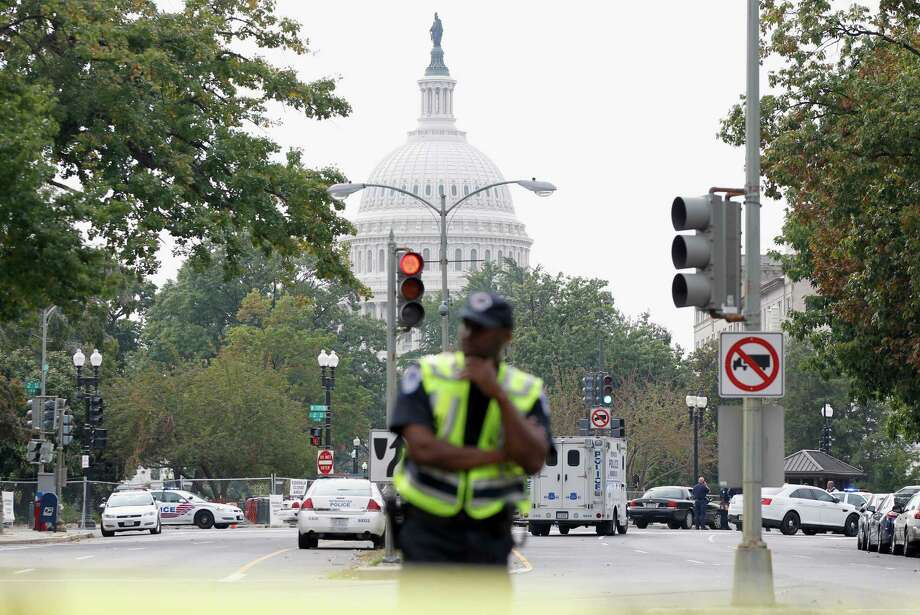 A Washington police officer stands guard on Capitol Hill in Washington, Thursday, Oct. 3, 2013, after a report of a shooting. A police officer was reported injured after gunshots at the U.S. Capitol, police said Thursday. They locked down the entire complex, at least temporarily derailing debate over how to end a government shutdown. Photo: AP