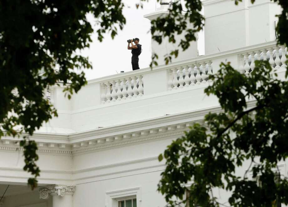 A member of the Secret Service Counter Assault team watches from the roof of the White House in Washington to survey the area, Thursday, Oct. 3, 2013, after reports of shot being fired on Capitol Hill. A police officer was reported injured after gunshots at the U.S. Capitol, police said Thursday. They locked down the entire complex, at least temporarily derailing debate over how to end a government shutdown. Photo: AP