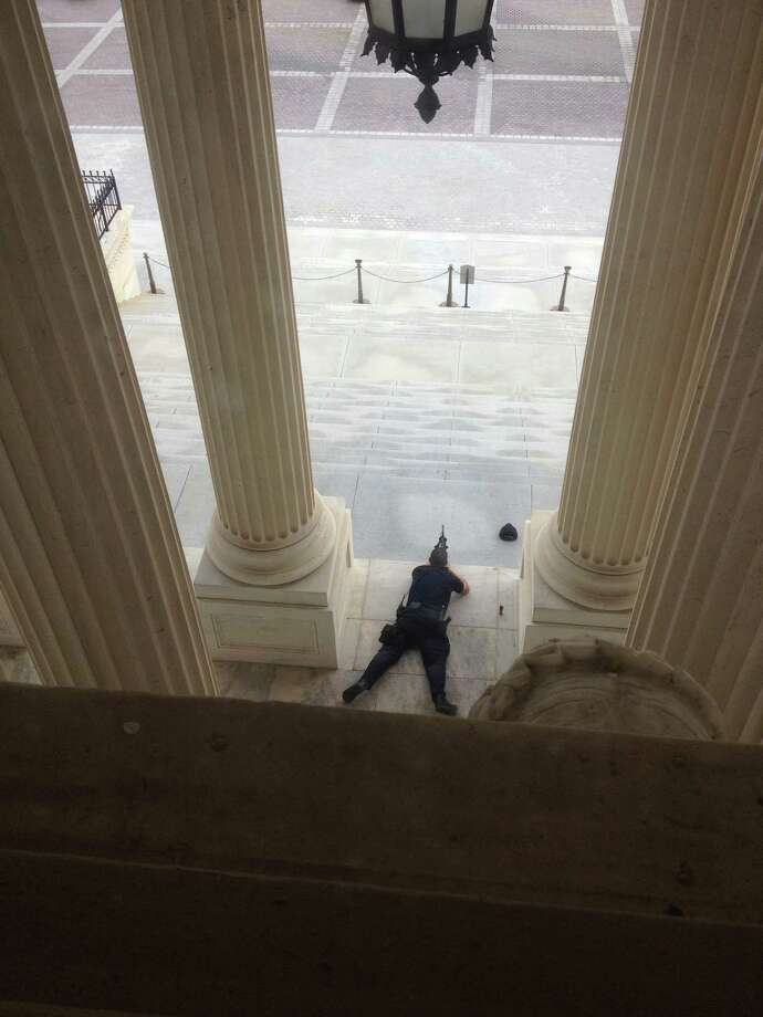 A U.S. Capitol police officer lies on the steps of the Senate with a gun drawn in response to a report of shots fired Thursday, Oct. 3, 2012. A police officer was reported injured after gunshots at the U.S. Capitol. They locked down the entire complex, at least temporarily derailing debate over how to end a government shutdown. (AP Photo/The Tampa Bay Times, Alex Leary) TAMPA OUT; CITRUS COUNTY OUT; PORT CHARLOTTE OUT; BROOKSVILLE HERNANDO OUT; USA TODAY OUT; MAGS OUT Photo: AP