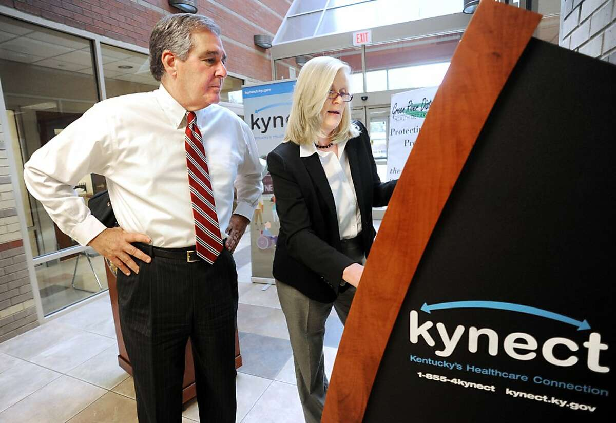 Carrie Banahan, head of Kentucky's state exchange, shows Lt. Gov. Jerry Abramson an information kiosk.
