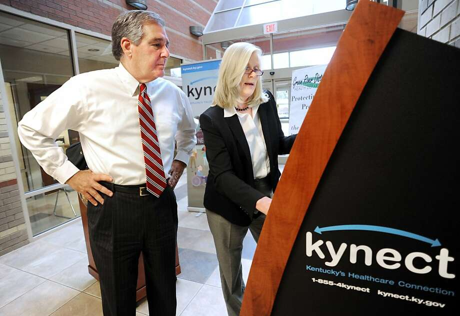 Carrie Banahan, head of Kentucky's state exchange, shows Lt. Gov. Jerry Abramson an information kiosk. Photo: Gary Emord-Netzley, Associated Press
