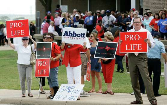 People hold signs protesting against State Sen. Wendy Davis as her supporters line up in the background outside the venue hosting a rally Thursday, Oct. 3, 2013, in Haltom City, Texas. Davis was expected to formally announce her campaign for governor Thursday, becoming the first Democrat to make an official bid for a statewide office. (AP Photo/LM Otero) Photo: LM Otero, Associated Press / AP