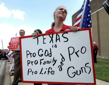 Davonia Leach of Burleson, Texas, holds a sign  protesting against State Sen. Wendy Davis outside the venue hosting a rally Thursday, Oct. 3, 2013, in Haltom City, Texas. Davis was expected to formally announce her campaign for governor Thursday, becoming the first Democrat to make an official bid for a statewide office. (AP Photo/LM Otero) Photo: LM Otero, Associated Press / AP