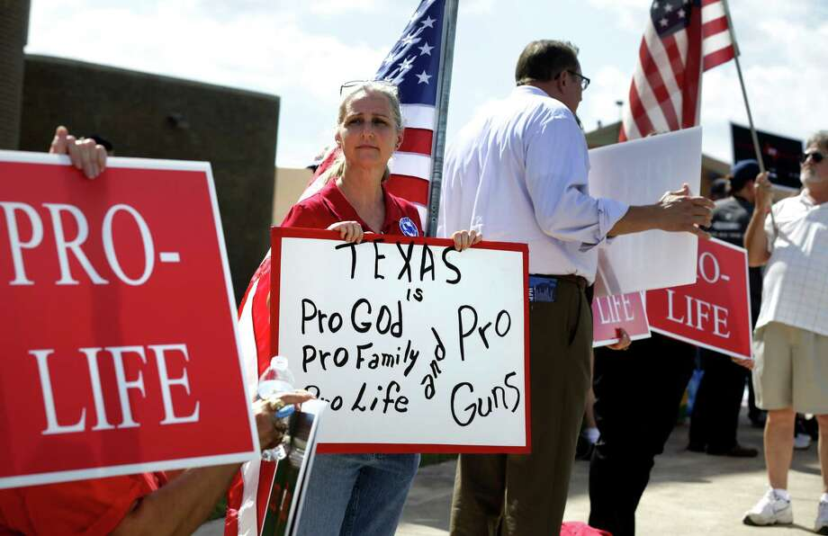 Davonia Leach, center, of Burleson, TX, holds protest signs outside where Senator Wendy Davis is to announce her candidacy for Texas Governor at W.G. Thomas Coliseum in Haltom City, TX, Oct. 3, 2013. Photo: Bob Owen, San Antonio Express-News / ©2013 San Antonio Express-News