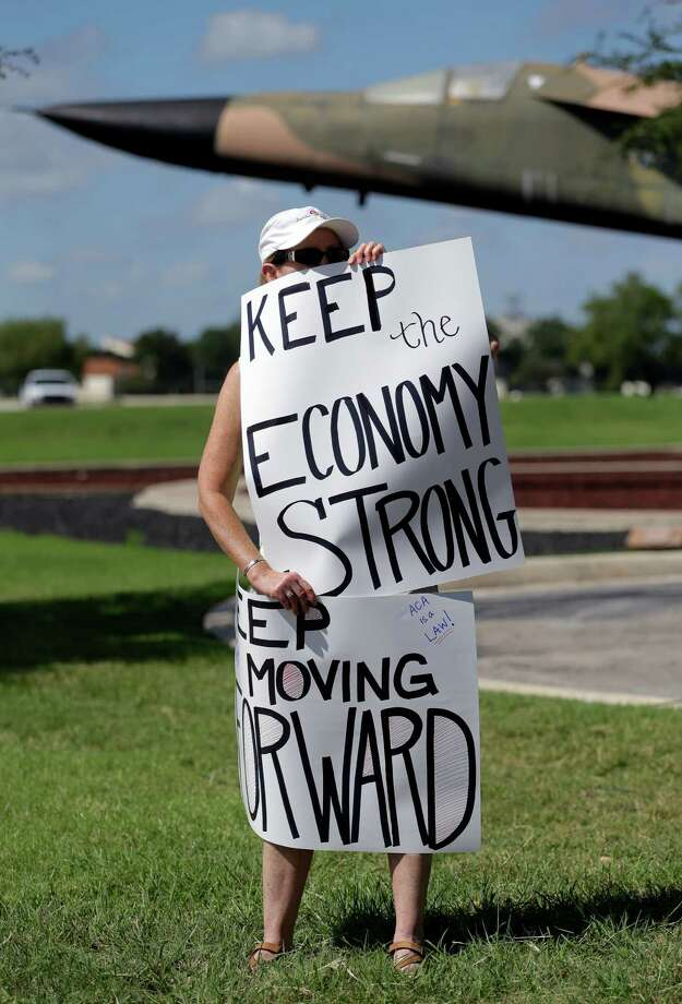 A protester for federal workers idled by the government shutdown holds signs outside the San Antonio office of U.S. Sen. Ted Cruz, R-Texas, Thursday, Oct. 3, 2013, in San Antonio. (AP Photo/Eric Gay) Photo: Eric Gay, Associated Press / AP
