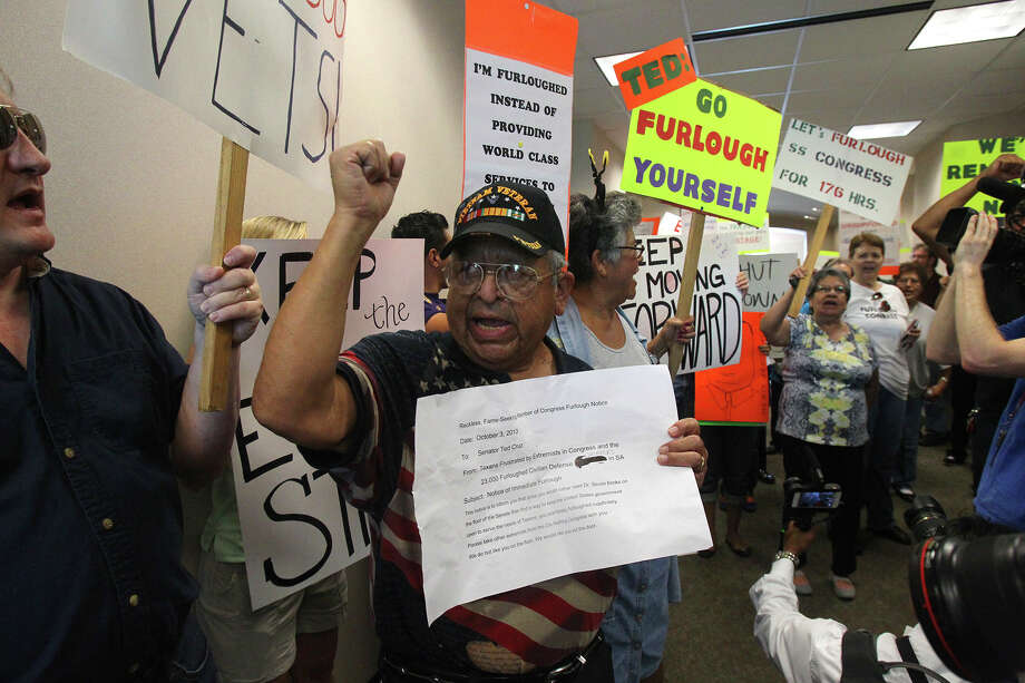 "Raul Sanchez (center) raises his arm and holds what protesters called "" a notice of immediate furlough"" for U.S. Senator Ted Cruz during a demonstration Thursday October 3, 2013 at Cruz's office at Port San Antonio. Federal workers, union members and others gathered in front of and inside of a building there that houses Cruz's office to express their disapproval of Cruz and the recent government shutdown. Photo: JOHN DAVENPORT, SAN ANTONIO EXPRESS-NEWS / ©San Antonio Express-News/Photo may be sold to the public"