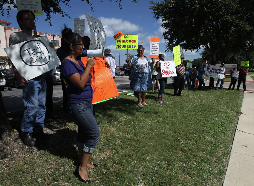 Union worker Marisa Gonzalez (left, holding bullhorn) chants during a demonstration Thursday October 3, 2013 in front of U.S. Senator Ted Cruz's office at Port San Antonio. Federal workers, union members and others gathered in front of and inside of a building there that houses Cruz's office to express their disapproval of Cruz and the recent government shutdown.