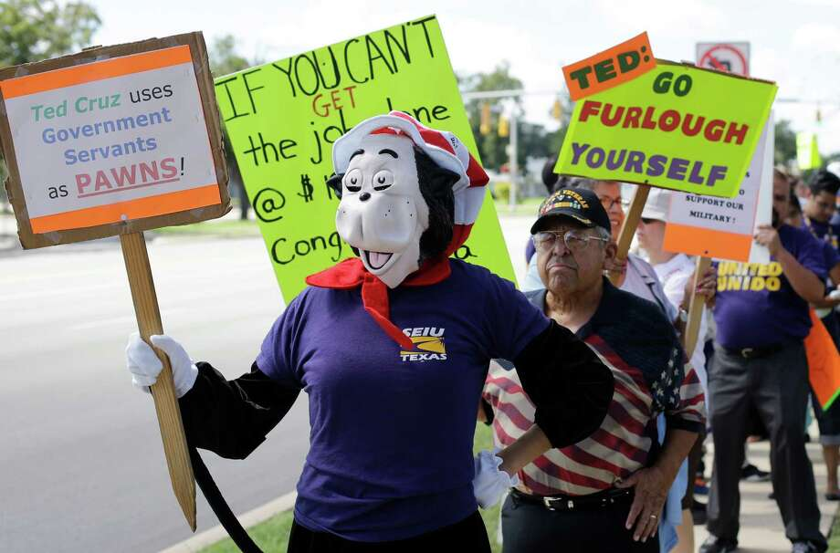 Protesters for federal workers idled by the government shutdown gather outside the San Antonio office of U.S. Sen. Ted Cruz, R-Texas, Thursday, Oct. 3, 2013, in San Antonio. (AP Photo/Eric Gay) Photo: Eric Gay, Associated Press / AP