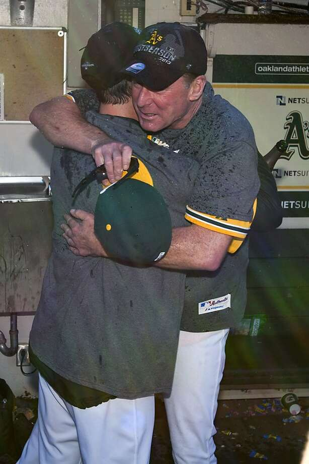 Bob Melvin gets a hug after the A's clinched - a day when moisture in the dugout came from bottles, not plumbing. Photo: Jason O. Watson, Getty Images