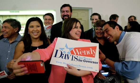 Texas Sen. Leticia Van DePutte, center, takes a photo of herself and others gathered for an announcement watch party for State Sen. Wendy Davis, Thursday, Oct. 3, 2013, in San Antonio. Davis formally announced her campaign for governor, becoming the first Democrat to make an official bid for a statewide office. (AP Photo/Eric Gay) Photo: Eric Gay, Associated Press / AP