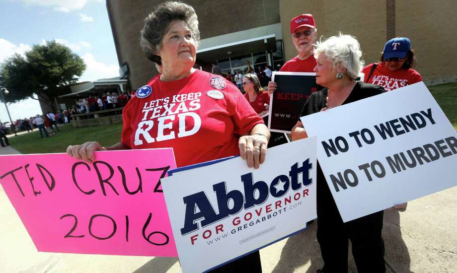 Maggie Wright, left, of Burleson, TX, holds protest signs in front of the venue where Senator Wendy Davis will announce her canditace for Texas Governor in Haltom City, TX. Photo: Bob Owen, San Antonio Express-News / ©2013 San Antonio Express-News