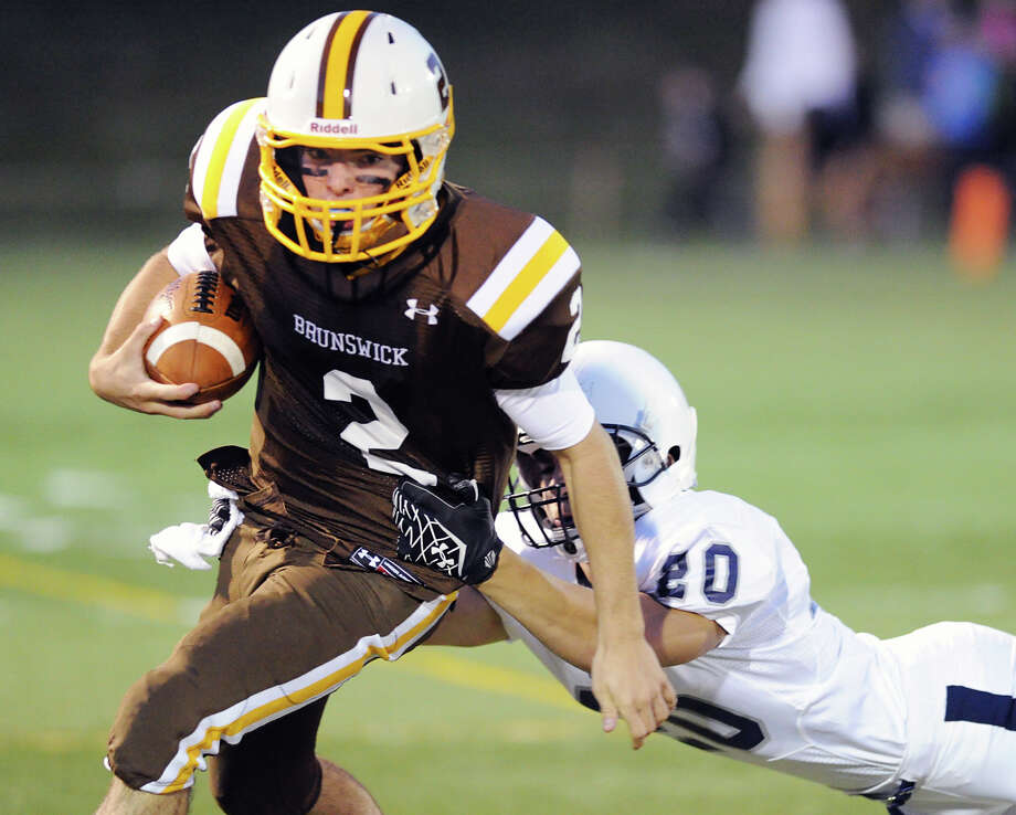 Brunswick quarterback,Billy O'Malley (# 2), left, runs the ball as Kent's Matt LaPorta (# 20) attempts a to tackle during the high School football game between Brunswick School and Kent School at Brunswick in Greenwich, Friday night, Sept. 20, 2013. Photo: Bob Luckey / Greenwich Time