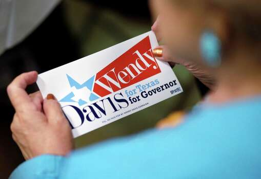 """A supporter holds a """"Wendy Davis for Governor"""" sticker during an announcement watch party for State Sen. Wendy Davis, Thursday, Oct. 3, 2013, in San Antonio. Davis formally announced her campaign for governor, becoming the first Democrat to make an official bid for a statewide office. (AP Photo/Eric Gay) Photo: Eric Gay, Associated Press / AP"""
