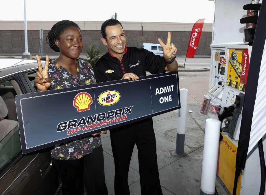 Helio Castroneves, driver of the No.3 Shell V-Power car for Penske Racing surprises fans with free fuel and prizes during an event Thursday, Oct. 3, 2013 near the track for the Shell-Pennzoil Grand Prix of Houston in Houston. Photo: Bob Levey, Associated Press
