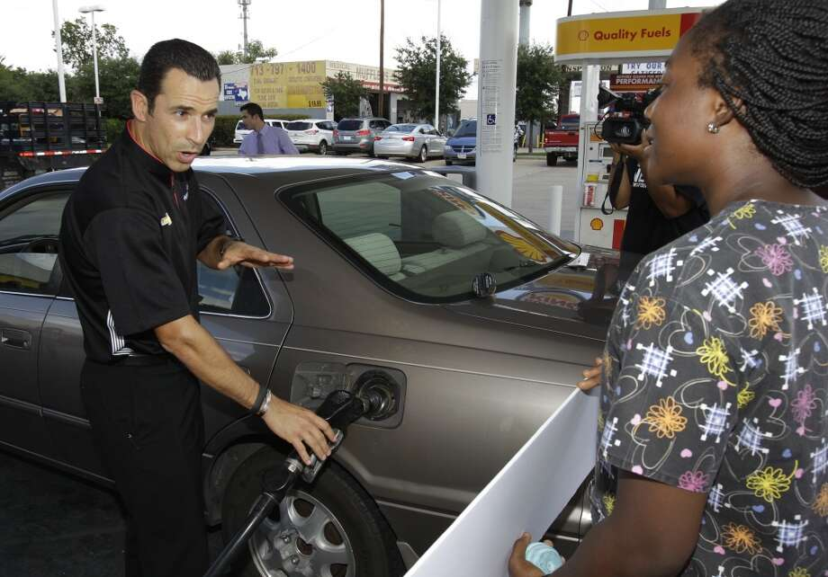 IndyCar driver Helio Castroneves pumps gas for customer Folasade Dage of Houston at a Shell station where she received a free tank of gas and Grand Prix of Houston tickets in a promotion Thursday, Oct. 3, 2013, in Houston.  Helio surprised customers and gave them a free tank of gas and the choice of prizes that included a ride in a two-seater IndyCar, $2,500 worth of Shell V-Power Gasoline, and tickets to the Shell-Pennzoil Grand Prix of Houston. The first customer took the first place prize of $2,500 worth of gas. Photo: Melissa Phillip, Houston Chronicle