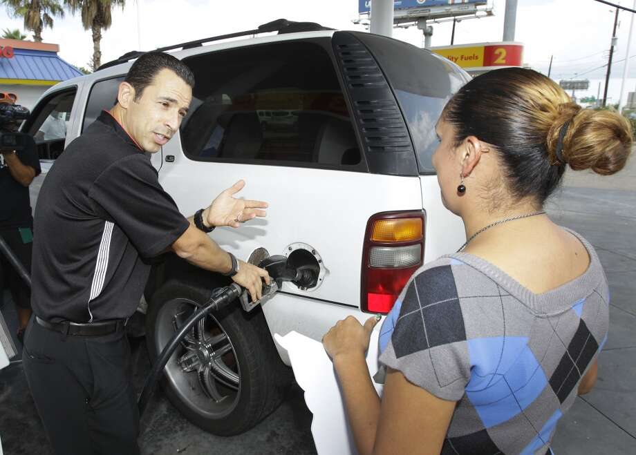IndyCar driver Helio Castroneves pumps gas for customer Claudia Najera of Houston at a Shell Station where she received a free tank of gas and Grand Prix of Houston tickets in a promotion Thursday, Oct. 3, 2013, in Houston.  Helio surprised customers and gave them a free tank of gas and the choice of prizes that included a ride in a two-seater IndyCar, $2,500 worth of Shell V-Power Gasoline, and tickets to the Shell-Pennzoil Grand Prix of Houston. The first customer took the first place prize of $2,500 worth of gas. Photo: Melissa Phillip, Houston Chronicle