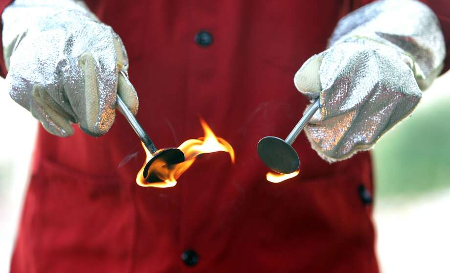 Shell Oil Company's Jim Macias holds engine valves on fire to demonstrate how much fuel a dirty valve can absorb during a tour of the Shell Research Center Tuesday, June 25, 2013, in Houston. ( James Nielsen / Houston Chronicle ) Photo: Houston Chronicle