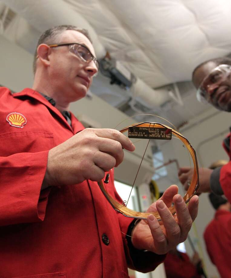 Shell Oil Company's Ron Skelton left, holds a Capillary Gas Chromatography Column as Autoblog.com's Jonathon Ramsey looks on during a tour of the Shell Research Center Tuesday, June 25, 2013, in Houston. ( James Nielsen / Houston Chronicle ) Photo: Houston Chronicle