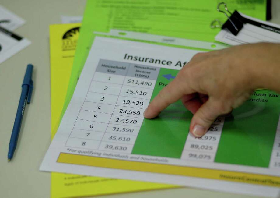 A volunteer counselor with Insure Central Texas uses a chart to explain health insurance options last week as hospitals, clinics and charities helped uninsured Texans on the health care exchanges. Photo: Eric Gay, Associated Press / AP