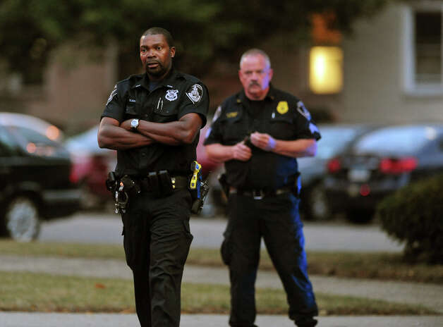 Stamford police officers stand guard at the Woosdside Green Condominiums on Summer Street in Stamford, Conn. on Thursday October 3, 2013. A woman who was killed by Washington DC police earlier in the day lived in one of the condos. Photo: Christian Abraham / Connecticut Post