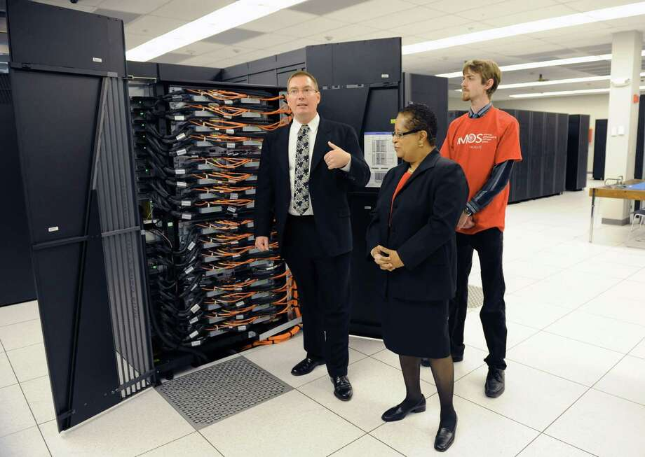 RPI computer science professor Christopher Carothers, left, RPI  president Shirley Ann Jackson, and student Ben Vreeland, right, unveil super computer AMOS  Thursday morning, Oct. 3, 2013, during a press conference at the RPI/IBM Supercomputer facility in North Greenbush, N.Y. (Michael P. Farrell/Times Union) Photo: Michael P. Farrell / 00024116A