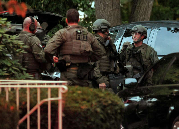 Members of the FBI suit up at the Woodside Green Condominiums on Summer Street in Stamford, Conn. on Thursday October 3, 2013. A woman who was killed by Washington DC police earlier in the day lived in one of the condos. Photo: Christian Abraham / Connecticut Post