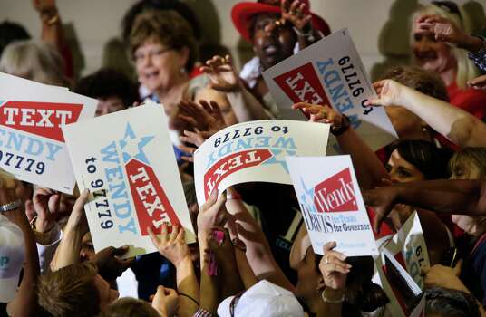 Wendy Davis posters are passes out to the crowd before Senator Wendy Davis announced her candidacy for Texas Governor at W.G. Thomas Coliseum in Haltom City, TX, Oct. 3, 2013. Photo: Bob Owen, San Antonio Express-News / ©2013 San Antonio Express-News