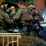 Members of the FBI suit up at the Woodside Green Condominiums on Summer Street in Stamford, Conn. on Thursday October 3, 2013. A woman who was killed by Washington DC police earlier in the day lived in one of the condos.