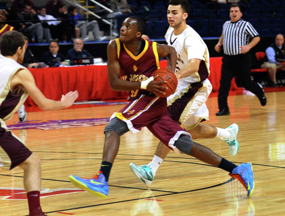 St. Joseph's #11 Quincy McKnight drives the ball to the basket, during Northeast Christmas Classic basketball tournament action against Monsignor Farrell at the Webster Bank Arena in Bridgeport, Conn. on Thursday December 27, 2012. Photo: Christian Abraham / Connecticut Post