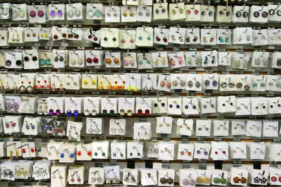 A wall filled with earrings at Bella Jewelry in Harwin Central Mart Tuesday October 1, 2013.The Hucksters agency is focused on bring more attention to there clients on Harwin Drive shopping district in Houston, Texas. Photo: Billy Smith II, Chronicle / © 2013 Houston Chronicle