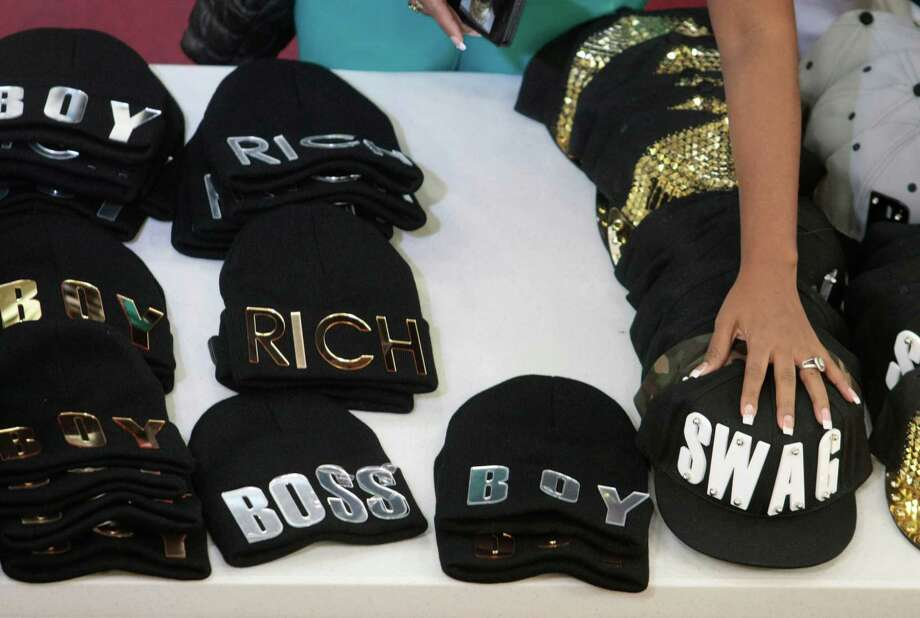 Hats with bold writing at the Jewelry Factory at Harwin Central Mart Tuesday October 1, 2013.The Hucksters agency is focused on bring more attention to there clients on Harwin Drive shopping district in Houston, Texas. Photo: Billy Smith II, Chronicle / © 2013 Houston Chronicle