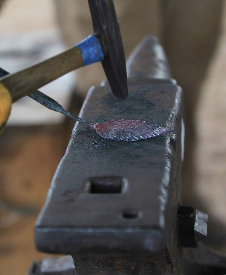 """David Koenig makes a leaf out of a piece of metal, pounding the shape out on an anvil as internationally acclaimed Virginia blacksmith/iron smelter Lee Sauder was demonstrating how to build a """"bloom iron"""" furnace in which he will produce iron as the ancient people did, in Oldenburg, which is near La Grange, Wednesday,Oct. 2, 2013, in Oldenburg. Photo: Karen Warren, Houston Chronicle / © 2013 Houston Chronicle"""